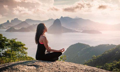 Woman Sat Meditating on a Hill