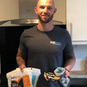 Brett Hadley wearing an eatlean tshirt holding eatlean products