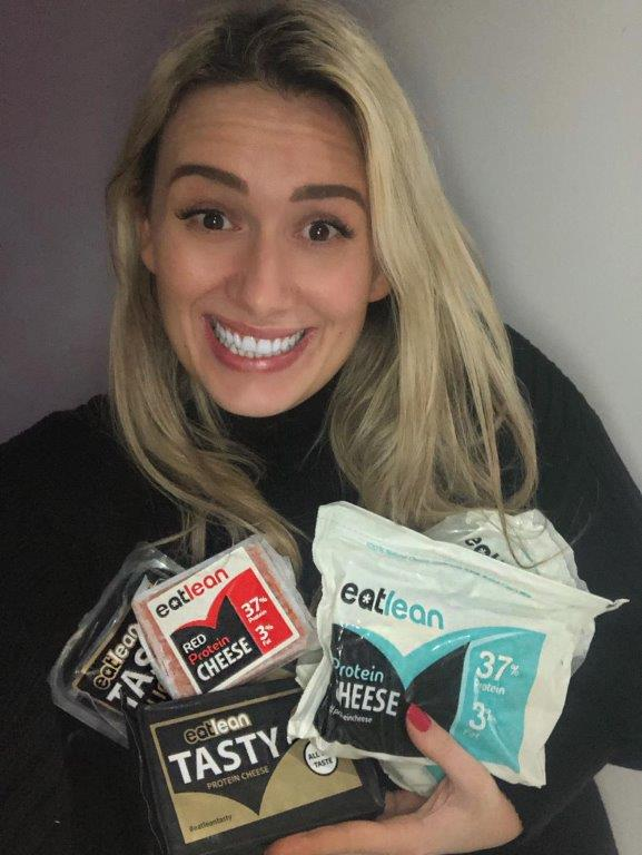 Grainne Mear Bullen smiling whilst holding a range of eatlean products