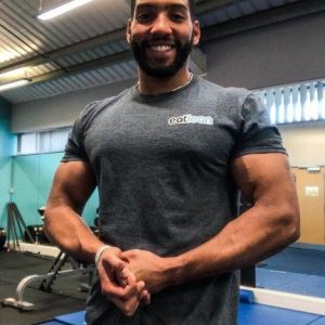 Joe Foxton posing in a gym with his eatlean tshirt
