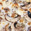Close up of an extra cheesy mushroom pizza
