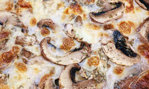 Close up of an extra cheesy mushroom pizza