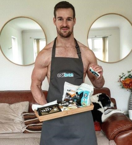 Tom Charlesworth topless in an Eatlean apron holding a tray full of Eatlean products
