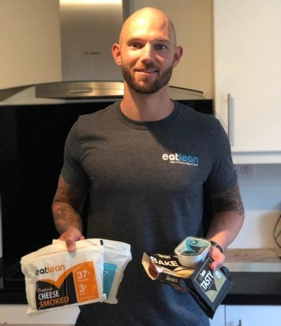 Brett Hadley performance and fat loss nutritionist wearing an Eatlean t-shirt and holding a selection of Eatlean products