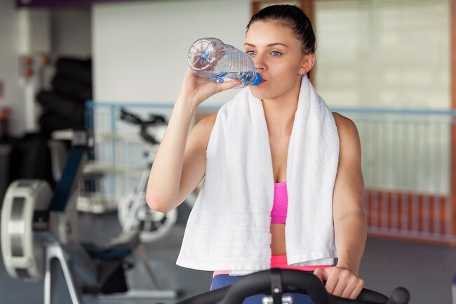 Woman drinking water in the gym